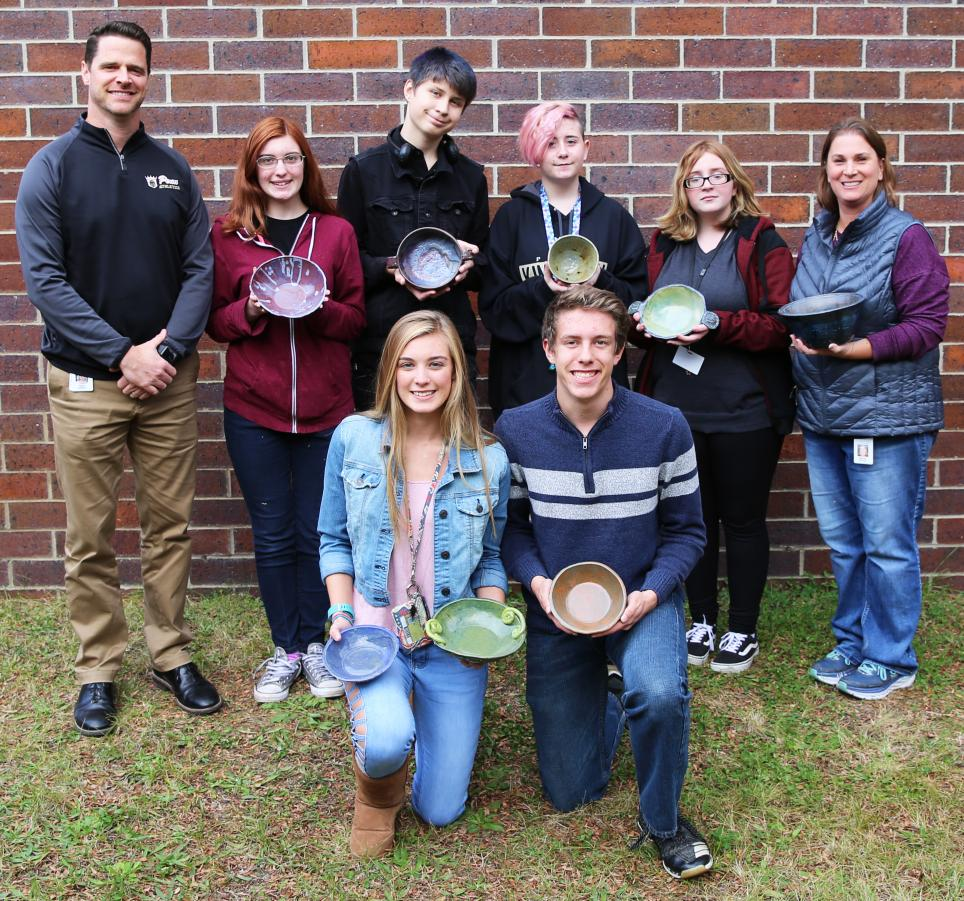 Penn High School Principal Sean Galiher, Ceramics Instructor Becky Brown with Penn Ceramics students who made food-safe ceramic bowls as a fundraiser for the Empty Bowls Project.