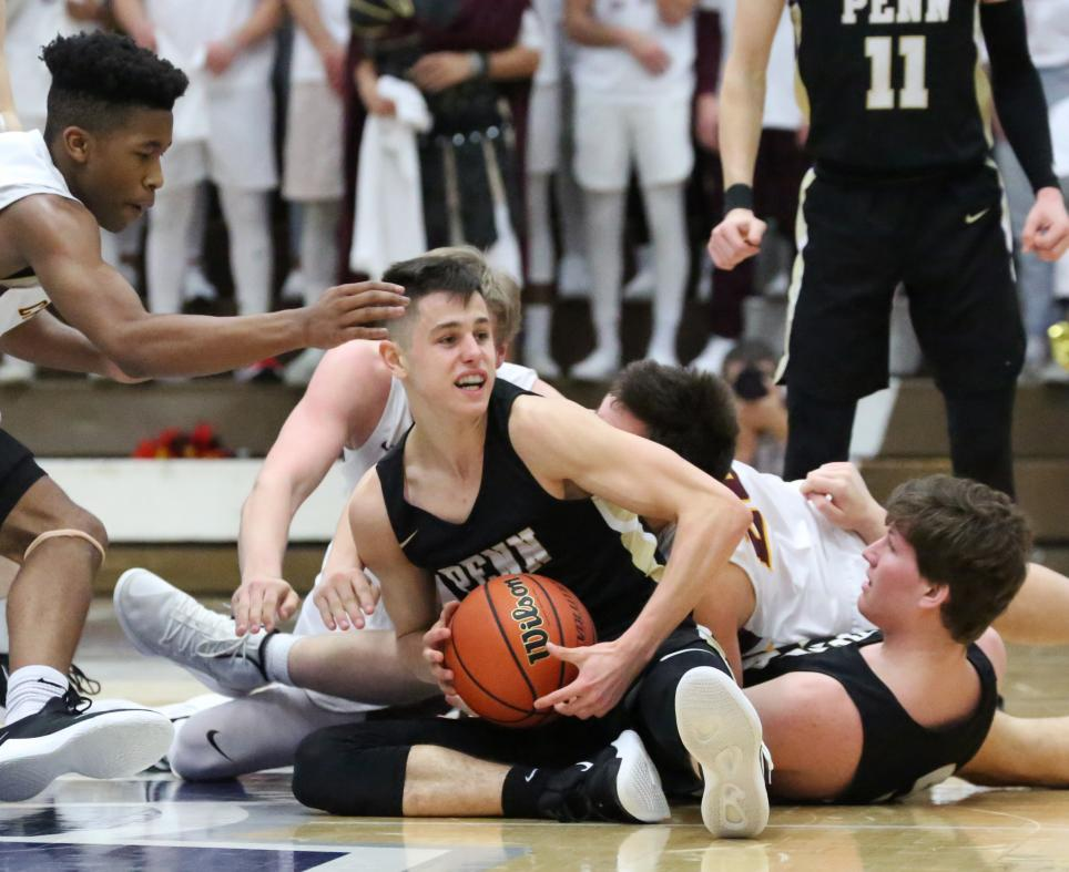 Penn Boys Basketball player Beau Ludwick outfights Chesterton players for control of the basketball.