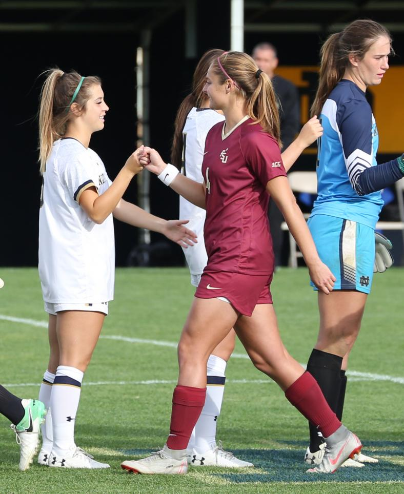 Former Penn stars Brooke VanDyck, left, and Kristina Lynch bump fists before the Notre Dame vs. Florida State Women's Soccer match.