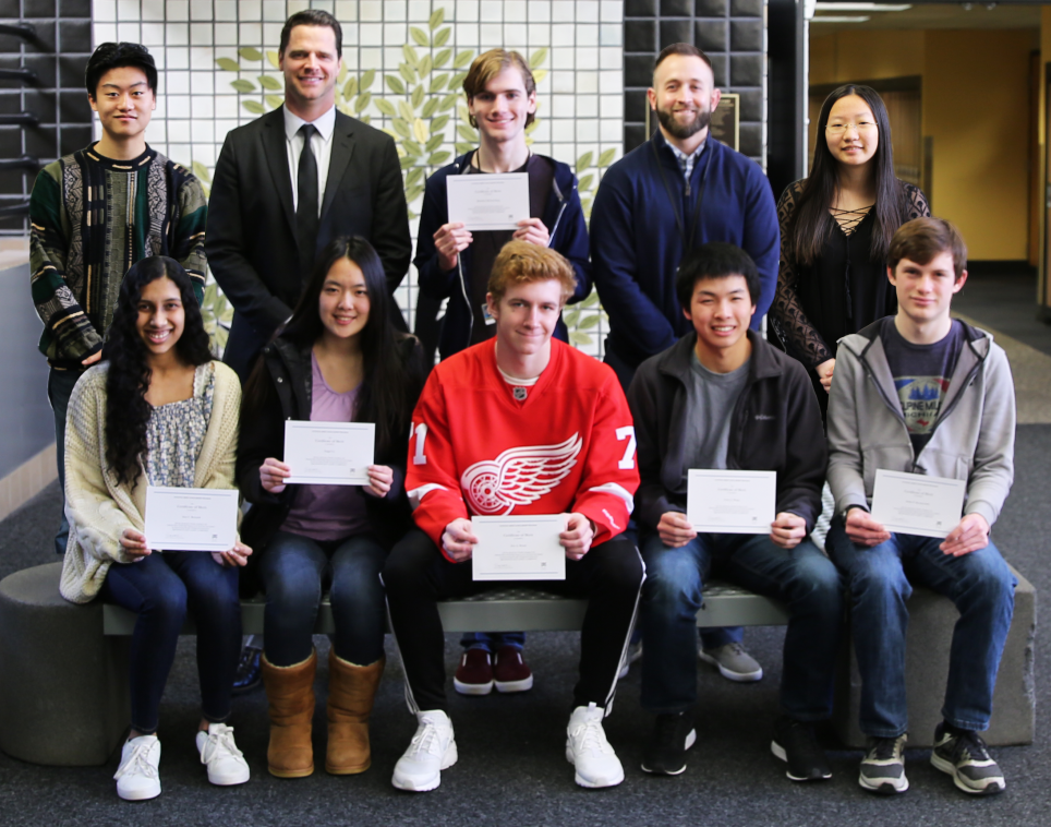 Penn High School Principal Sean Galiher and Counseling Center Director John Westra with Penn's eight National Merit Scholarship Finalists.