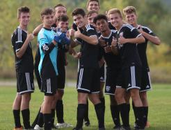 The Penn Boys Soccer team gives the thumbs up sign.