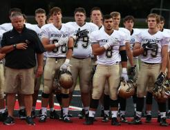 Penn Football Head Coach Cory Yeoman and Kingsmen players stand at attention for the playing of the National Anthem.