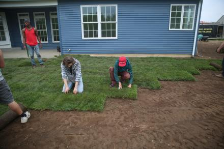 students laying sod at the house