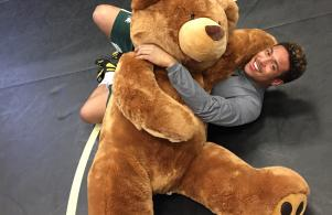 State champion wrestler Kobe Woods of Penn wrestles a giant teddy bear as part of a promotional campaign to college teddy bears for patients at a local children's hospital.