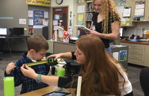 Students in Penn High School's Women in Engineering class measure Braylen for a project that will construct a balancing device that will also contain a language-acquisition I-pad.