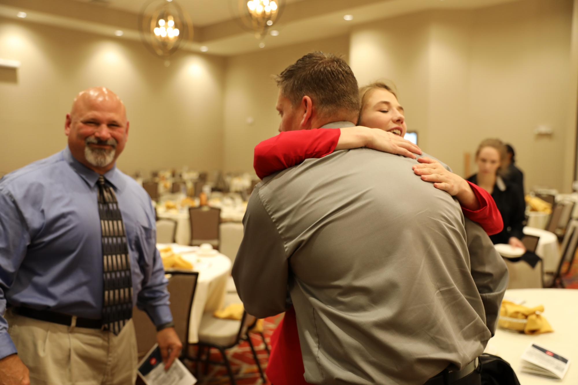 Sarah hugging her former Discovery wrestling coaches